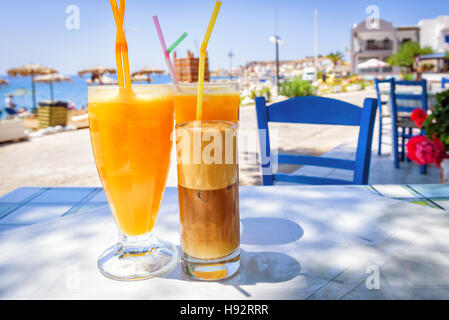 Glasses with orange juice and greek coffee frappe - Stock Photo