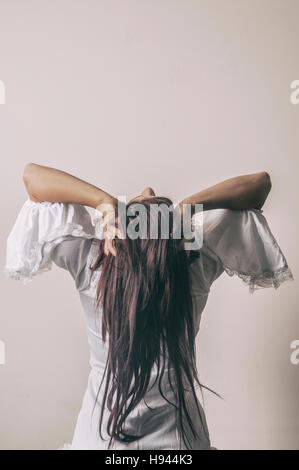 Rear view of a miserable woman head in hands - Stock Photo