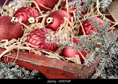 Glass Christmas ornaments packed in an old antique wooden box with snow covered pine boughs surrounding them. - Stock Photo