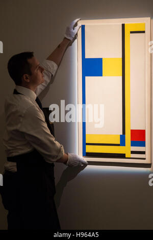 London, UK. 18 November 2016. A Sotheby's technician is handling the painting Composition Yellow, Blue, Black, Red - Stock Photo