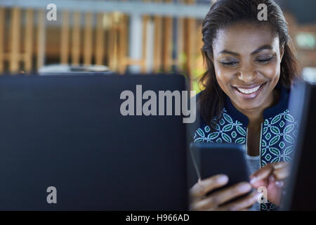 Smiling businesswoman texting with cell phone - Stock Photo