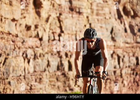 Male triathlete cyclist cycling along sunny rocks - Stock Photo