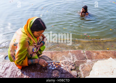 Women lighting candles for puja and bathing in Ganges river, Varanasi, India - Stock Photo