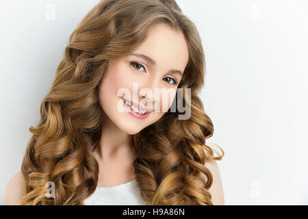 beautiful smiling girl with blond wavy hair by hairdresser
