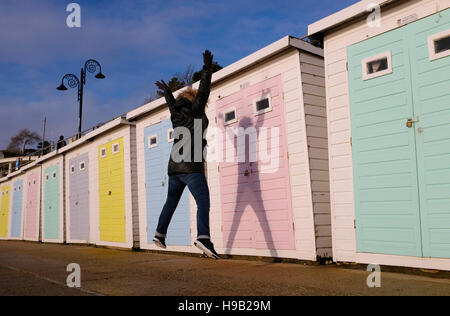 Woman star jumps creating shadow on beach huts at Lyme Regis Dorset November 2016 - Stock Photo