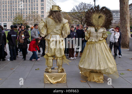 Two street artist standing still in front of a group of tourists in London's Southbank. - Stock Photo