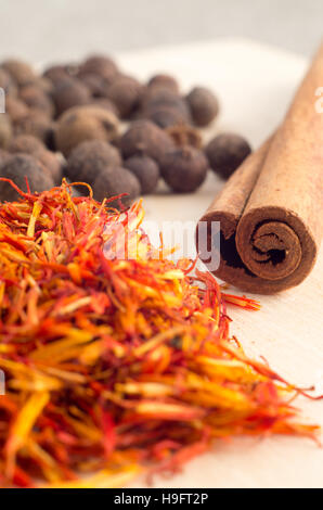 Condiments and spices - cinnamon sticks, allspice and fragrant saffron close-up with shallow depth of focus. - Stock Photo