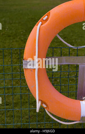 Orange life float. View of pool in the background unfocused. - Stock Photo