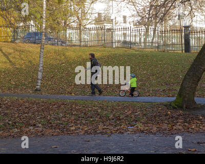 Glasgow park scene father and child led by lead on bicycle - Stock Photo