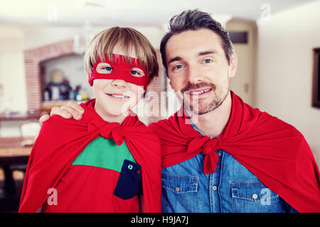Portrait of father and son pretending to be superhero in living room - Stock Photo