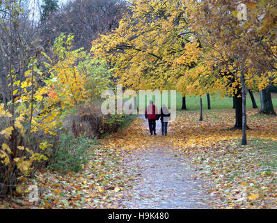 Glasgow park scene couple holding hands and walking on path or road - Stock Photo