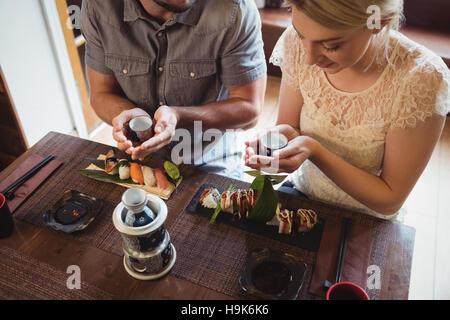 Couple having sake while eating sushi - Stock Photo