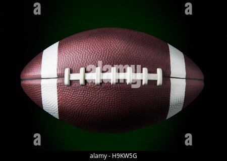 portrait of a american football ball in dark background - Stock Photo