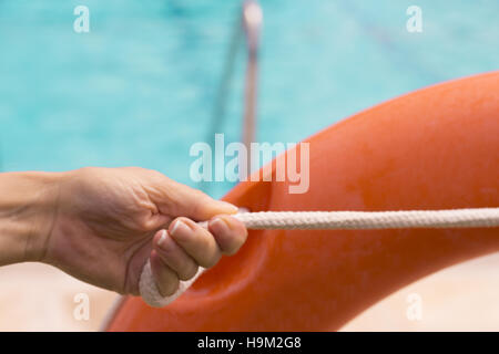 Woman catching lifeguard float in orange color - Stock Photo