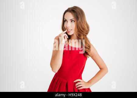 Portrait of a thoughtful woman in santa claus cloth looking away isolated on a white background - Stock Photo