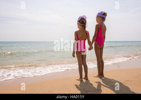 Two girls in bathing suits standing on the beach and look at the horizon - Stock Photo