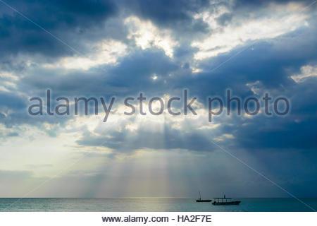 Sun burst through the clouds on the ocean - Stock Photo
