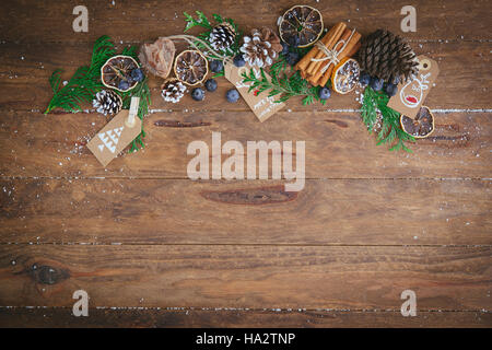 Christmas pine cones, pine branches, cinnamon sticks, dried oranges and tags - Stock Photo