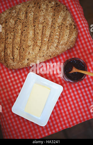 Fresh baked bread on tartan table background with butter and raspberry jam - Stock Photo