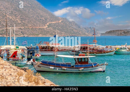 Traditional greek fishing boats in port near Aghios Nikolaos town on Crete island - Stock Photo