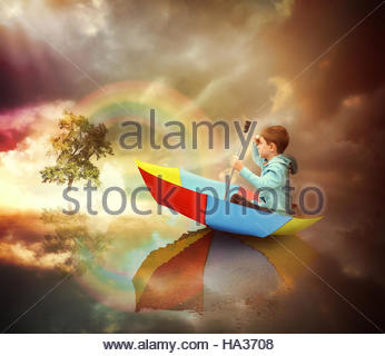 A little child is sitting in an umbrella boat looking at a distant tree of light with a rainbow for an imagination - Stock Photo