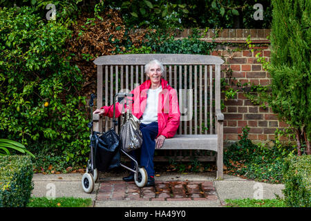 An Elderly Disabled Woman Sitting On A Bench, Sussex, UK - Stock Photo