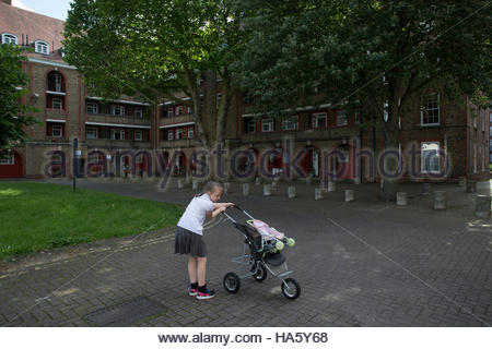 A young girl plays with her pram and doll in the grounds of the Wyndham and Comber Estate in Southwark South London, - Stock Photo