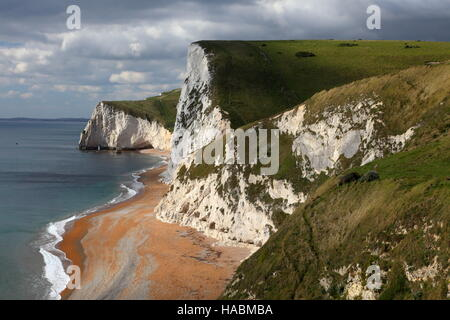 Dramatic sky and autumn sunshine over bay from Durdle Door towards Bat's Head, Dorset UK - Stockfoto