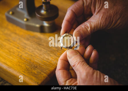 Horologist hand holding watch frame in workshop - Stock Photo