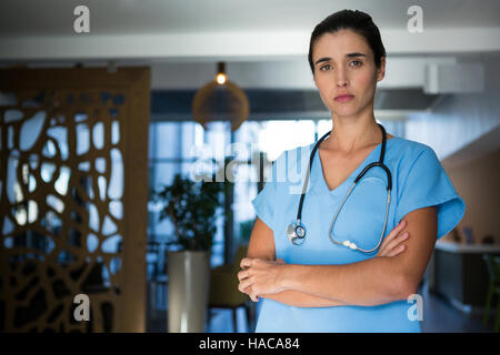 Portrait of female surgeon standing in hospital - Stock Photo