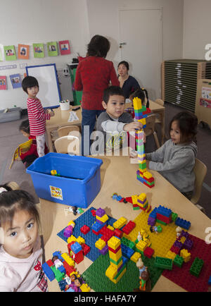 Young children build with Lego blocks at a nursery school in Manhattan on the Lower East Side. - Stock Photo