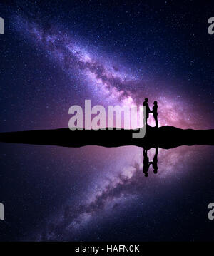 Milky Way with silhouette of people. Landscape with night starry sky and man and woman holding hands on the mountain - Stock Photo