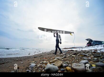 Vladivostok, Russia. 1st Dec, 2016. A man with his surfboard walking along the Ussuri Bay. Credit:  Yuri Smityuk/TASS/Alamy - Stockfoto