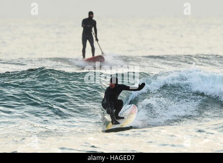 Vladivostok, Russia. 1st Dec, 2016. A surfer and a stand up paddle boarder riding a wave in the Ussuri Bay. Credit: - Stockfoto