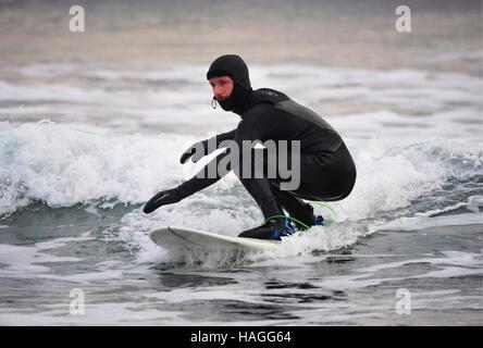 Vladivostok, Russia. 1st Dec, 2016. A surfer riding a wave in the Ussuri Bay. Credit:  Yuri Smityuk/TASS/Alamy Live - Stockfoto