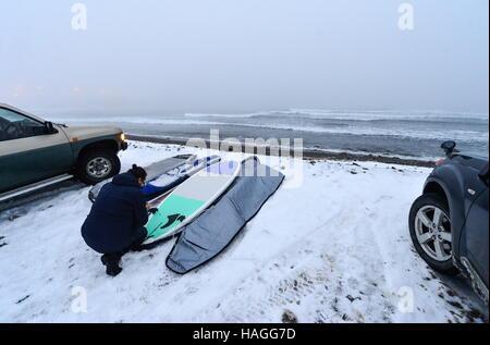Vladivostok, Russia. 1st Dec, 2016. A man with a stand up paddle board on the Ussuri Bay coast. Credit:  Yuri Smityuk/TASS/Alamy - Stockfoto