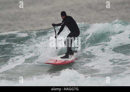 Vladivostok, Russia. 1st Dec, 2016. A man riding a wave on a stand up paddle board in the Ussuri Bay. Credit:  Yuri - Stockfoto