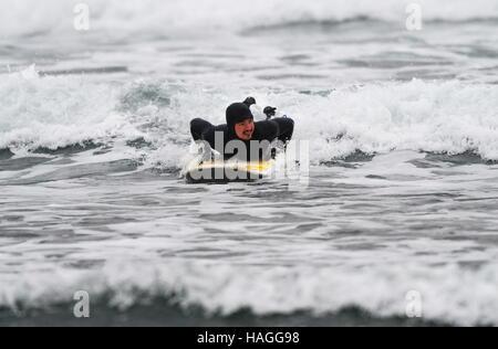 Vladivostok, Russia. 1st Dec, 2016. A man on a surfboard in the Ussuri Bay. Credit:  Yuri Smityuk/TASS/Alamy Live - Stockfoto