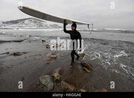 Vladivostok, Russia. 1st Dec, 2016. A man carries a surfboard in the Ussuri Bay. Credit:  Yuri Smityuk/TASS/Alamy - Stockfoto