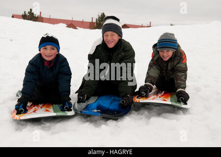 Portrait of cute boys being silly on a sled in the snow. - Stockfoto