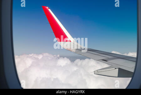 White clouds and blue sky as seen through window of an aircraft - Stock Photo