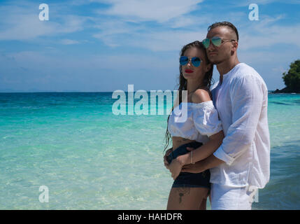 Sensual pretty couple wearing white clothes and sunglasses embracing on the beach and looking at the view over beautiful - Stock Photo