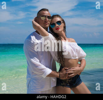 Sensual pretty couple wearing white clothes and sunglasses embracing on the beach and looking at the camera over - Stock Photo