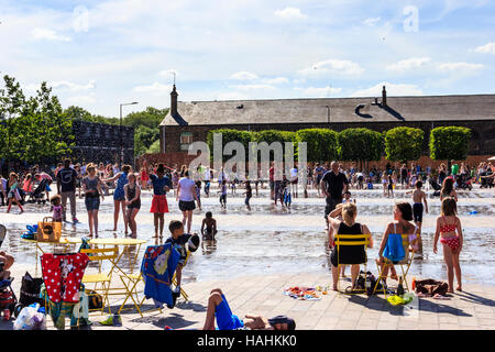 Sunbathing in Granary Square, King's Cross, London - Stock Photo