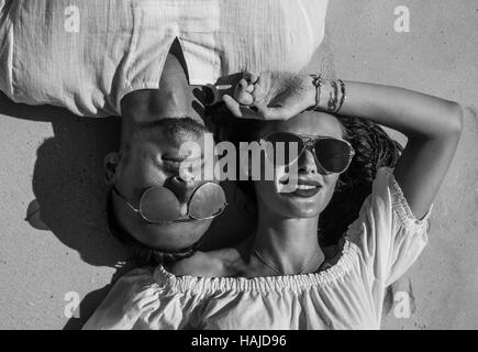 Top view closeup face of sensual pretty couple wearing white clothes and sunglasses smiling while laying on the - Stock Photo