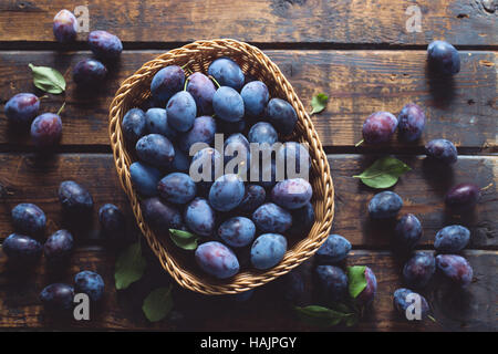 Freshly picked organic plums on a wooden table - Stock Photo