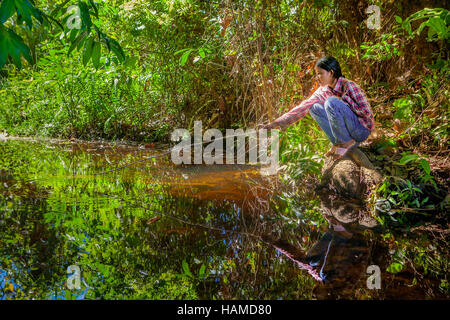 A young Khmer Cambodian woman squats beside a forest stream fishing for her family in Banteay Srei, Kingdom of Cambodia. - Stock Photo