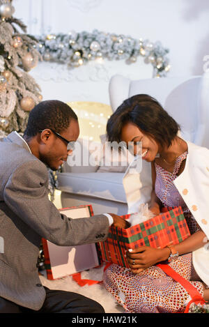 Happy Afro-american couple opening the prresent box and taking the small white fluffy rabbit out oh it, The girl - Stock Photo