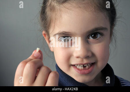 Proud young girl (age 6) holds her first falling milk teeth, looks at the camera. Childhood healthcare concept.real - Stock Photo