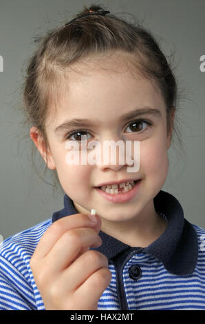 Happy young girl (age 6) holds her first falling milk teeth, looks at the camera. Childhood healthcare concept. - Stock Photo